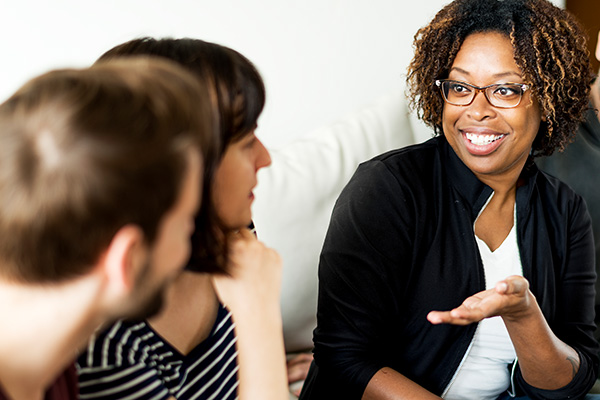 Young woman smiling and talking to two young adults