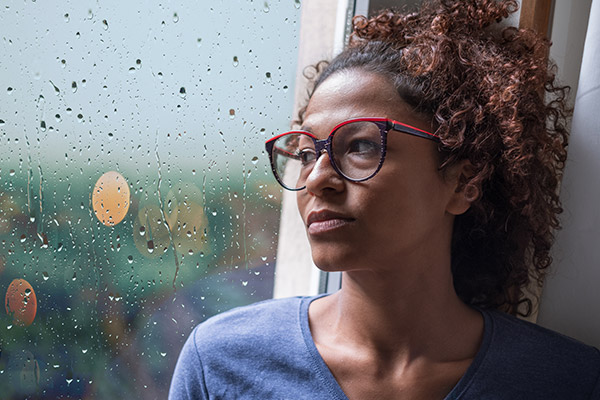 Young woman staring our window in deep thought