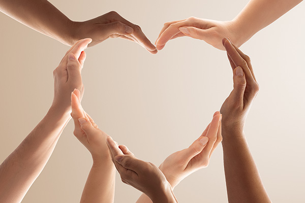 Four sets of hands forming a heart shape